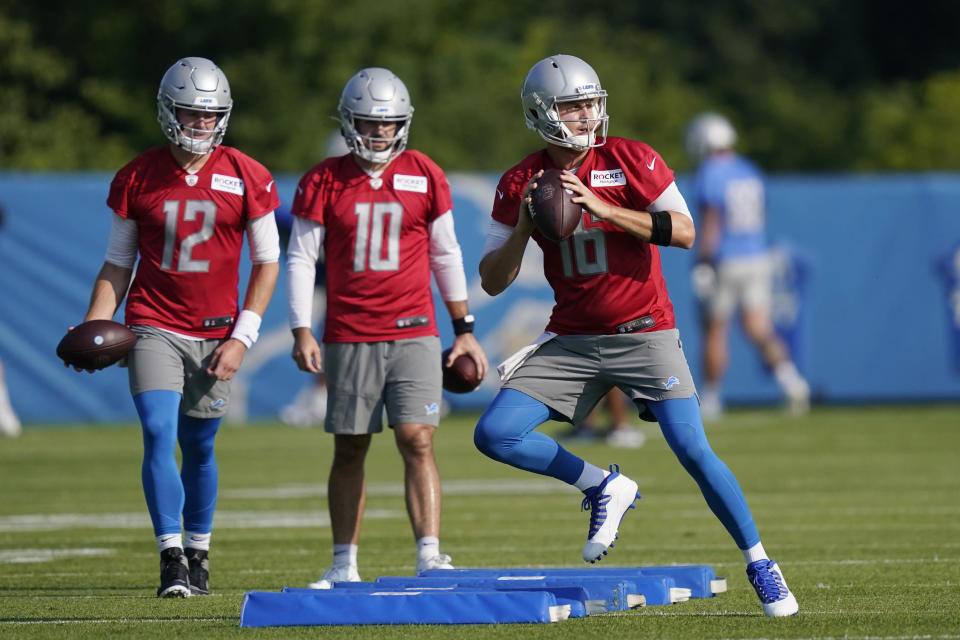 Detroit Lions quarterbacks Jared Goff, right, David Blough (10) and Tim Boyle (12) run through a drill at the Lions NFL football camp practice, Wednesday, July 28, 2021, in Allen Park, Mich. (AP Photo/Carlos Osorio)