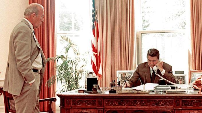 US Secretary of State George Shultz watches as US President Ronald Reagan speak on the phone