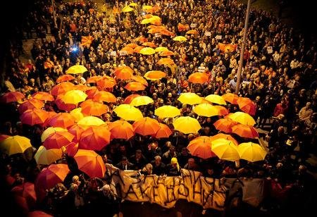 Protesters shout slogans while holding red and yellow umbrellas during demonstrations against an agreement that would ensure the wider official use of the Albanian language, in Skopje, Macedonia, March 1, 2017.  REUTERS/Stringer