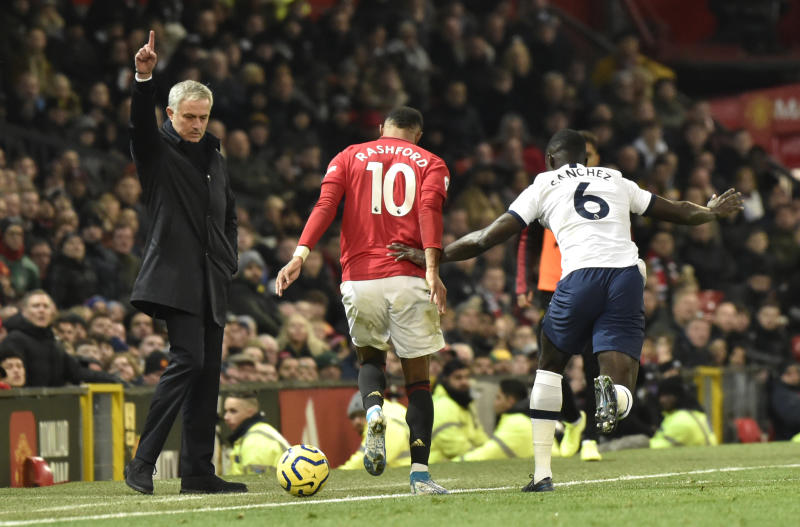 Tottenham's manager Jose Mourinho, left, reacts as Manchester United's Marcus Rashford, centre, and Tottenham's Davinson Sanchez challenge for the ball during the English Premier League soccer match between Manchester United and Tottenham Hotspur at Old Trafford in Manchester, England, Wednesday, Dec. 4, 2019. (AP Photo/Rui Vieira)