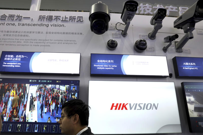 In this photo taken Tuesday, Oct. 23, 2018, a man stands near security cameras and display of facial tracking technologies by state-owned surveillance equipment manufacturer Hikvision at the Security China 2018 expo in Beijing, China. The Chinese video surveillance company says it is taking concern about the use of its technology seriously following a report that the U.S. may block several Chinese surveillance companies from buying American components. (AP Photo/Ng Han Guan)