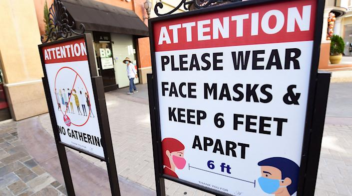 Signs reminding people of social distance and wearing face masks remain at a mall in Monterey Park, California, on June 14, 2021, a day before California's economy fully reopens since the state's first shutdown in March 2020 due to the coronavirus pandemic. (Frederic J. Brown/AFP via Getty Images)