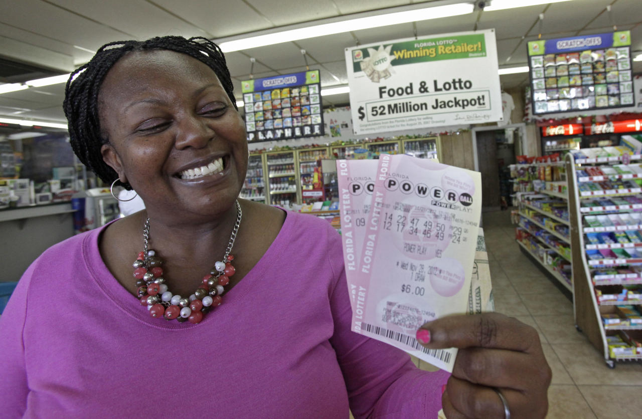 Felicia Ross shows off what she hopes will be the winning Powerball tickets at a convenience store, Tuesday, Nov. 27, 2012, in Orlando, Fla. The powerball jackpot is up over $500 million for Wednesday's drawing. (AP Photo/John Raoux)