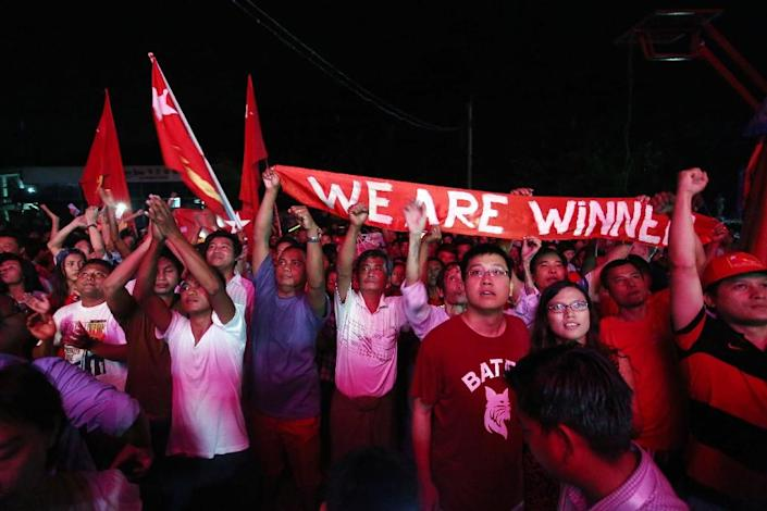 Supporters of Aung San Suu Kyi and her opposition party cheer as they watch polling station counts on a giant screen outside the party headquarters in Yangon on November 8, 2015 (AFP Photo/Ye Min Aung)