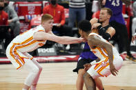 Toronto Raptors guard Malachi Flynn (8) grabs the ball away from Atlanta Hawks guard Kevin Huerter (3) and guard Brandon Goodwin (0) during the second half of an NBA basketball game Tuesday, April 13, 2021, in Tampa, Fla. (AP Photo/Chris O'Meara)
