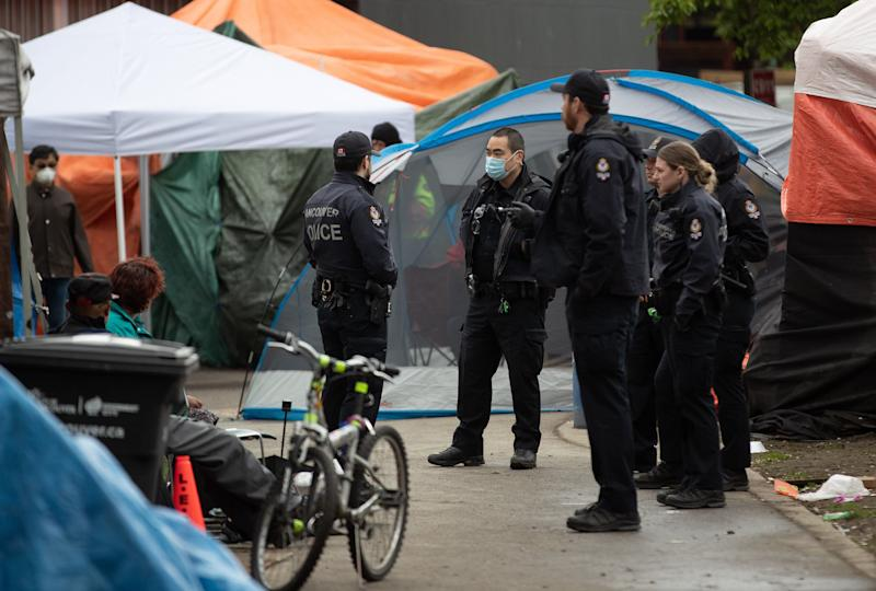 Police officers are seen at a homeless camp at Oppenheimer Park in the Downtown Eastside in Vancouver, on April 26, 2020. (Photo: Darryl Dyck/THE CANADIAN PRESS)