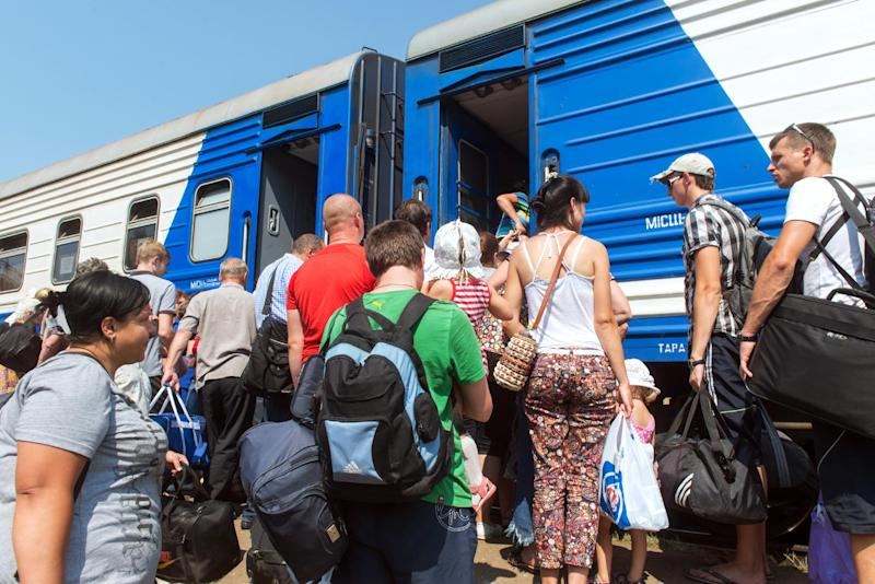 Ukrainian civilians board a special train for displaced people as they flee fighting in the eastern city of Svatovo, on August 12, 2014