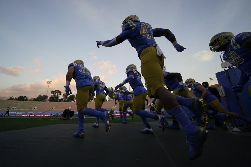 UCLA players enter the Rose Bowl before their game against rival USC on Dec. 12, 2020.