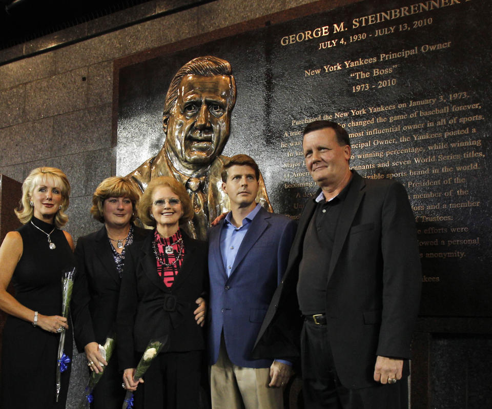 "FILE - In this Sept. 20, 2010, file photo, members of the Steinbrenner family pose in front of George Steinbrenner's monument during a ceremony dedicating a monument to the late Yankees principal owner George Steinbrenner before the Yankees baseball game against the Tampa Bay Rays at Yankee Stadium in New York. From left are Steinbrenner's two daughters Jennifer Steinbrenner Swindal, and Jessica Steinbrenner, George Steinbrenner's widow Joan, and their sons Hal Steinbrenner and Hank Steinbrenner. Henry ""Hank"" Steinbrenner died Tuesday, April 14, 2020, at his home in Clearwater, Fla. He was 63. (AP Photo/Kathy Willens, Pool, File)"