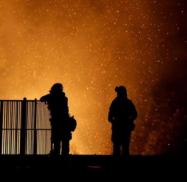 PHOTO: Burning embers swirl around firefighters as they stand guard at a home while battling the Carr Fire, west of Redding, Calif., July 27, 2018. (Fred Greaves/Reuters)