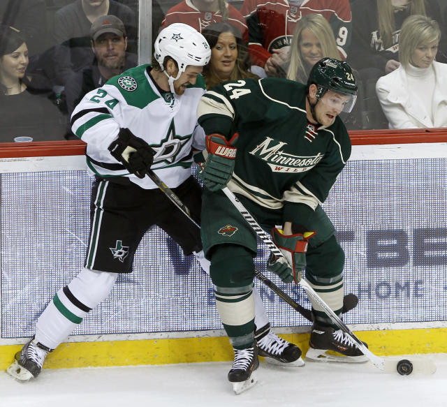 Minnesota Wild left wing Matt Cooke, right, controls the puck in front of Dallas Stars defenseman Jordie Benn, left, during the first period of an NHL hockey game in St. Paul, Minn., Saturday, Jan. 18, 2014. (AP Photo/Ann Heisenfelt)