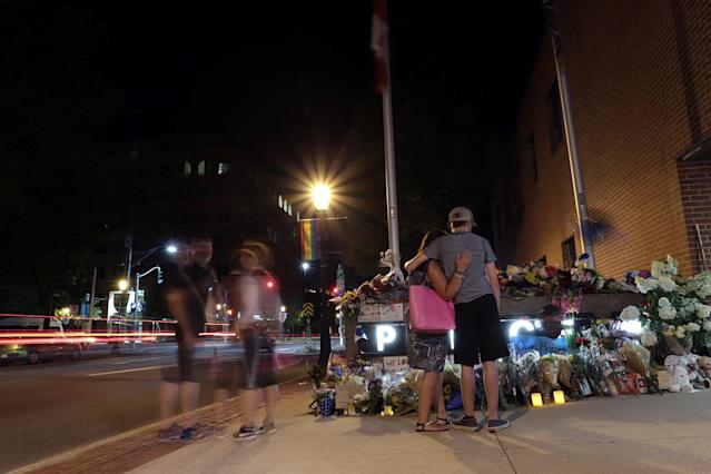 <p>Fredericton residents pay their respects at a makeshift shrine created in front of police headquarters after four people, including two police officers, were killed in a shooting in Fredericton on Aug. 10, 2018. (Photo from Reuters/Dan Culberson) </p>