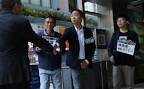 Winning candidate Kelvin Lam and activist Joshua Wong greet people and thank them for their support, outside of South Horizons Station, in Hong Kong
