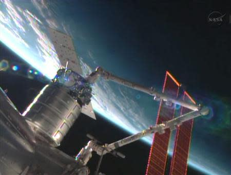 NASA handout still image from video shows unmanned US commercial cargo ship Cygnus being attached to the International Space Station