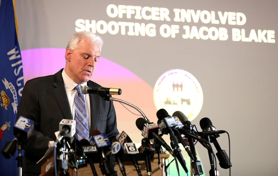 Kenosha County District Attorney Michael Graveley stands in front of microphones at a news conference