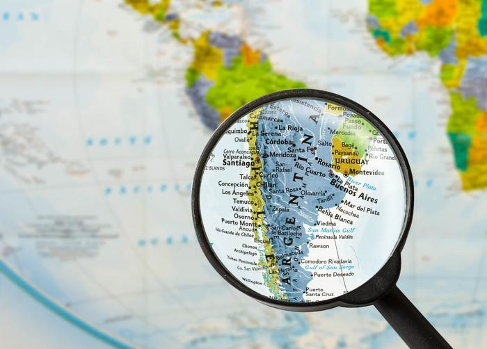A magnifying glass enlarges Argentina on a map of South America.