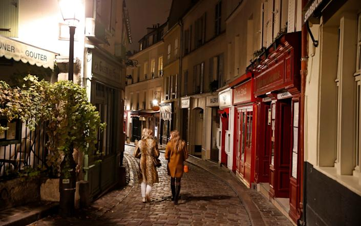 Women walk on a deserted street at night on the Butte Montmartre - Getty Images Europe