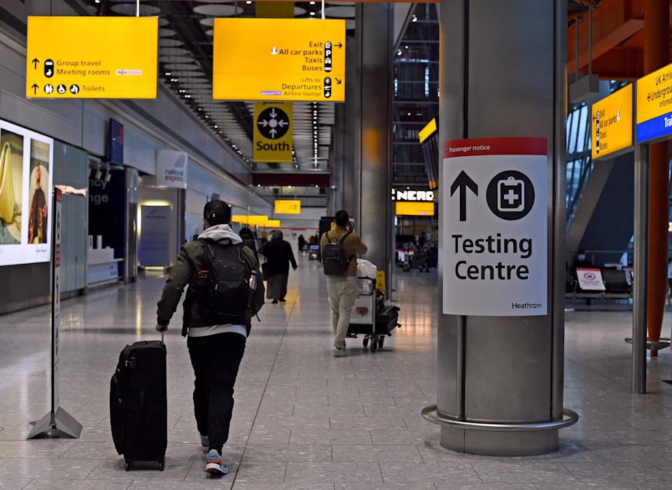 A passenger walks past a sign for the Covid testing centre in Heathrow's Terminal 5 (PA Wire)