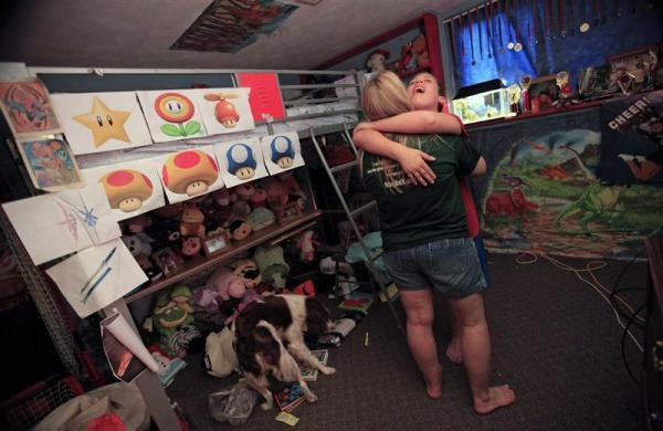 Parker Roos, who suffers from Fragile X, hugs his mother Holly after getting upset about not being able to find one of his inflatable lawn toys at his home in Canton, Illinois, April 3, 2012.