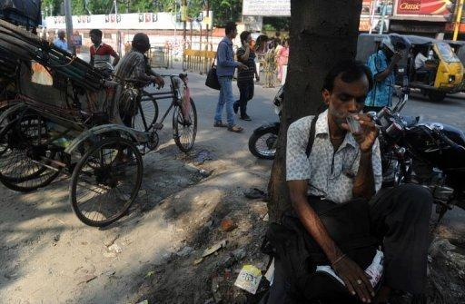 An Indian drinks tea at roadside shop in Siliguri on May 26. The Indian economy expanded by a much slower-than-expected 5.3 percent in the January-March quarter, official data showed, adding further pressure on the embattled government