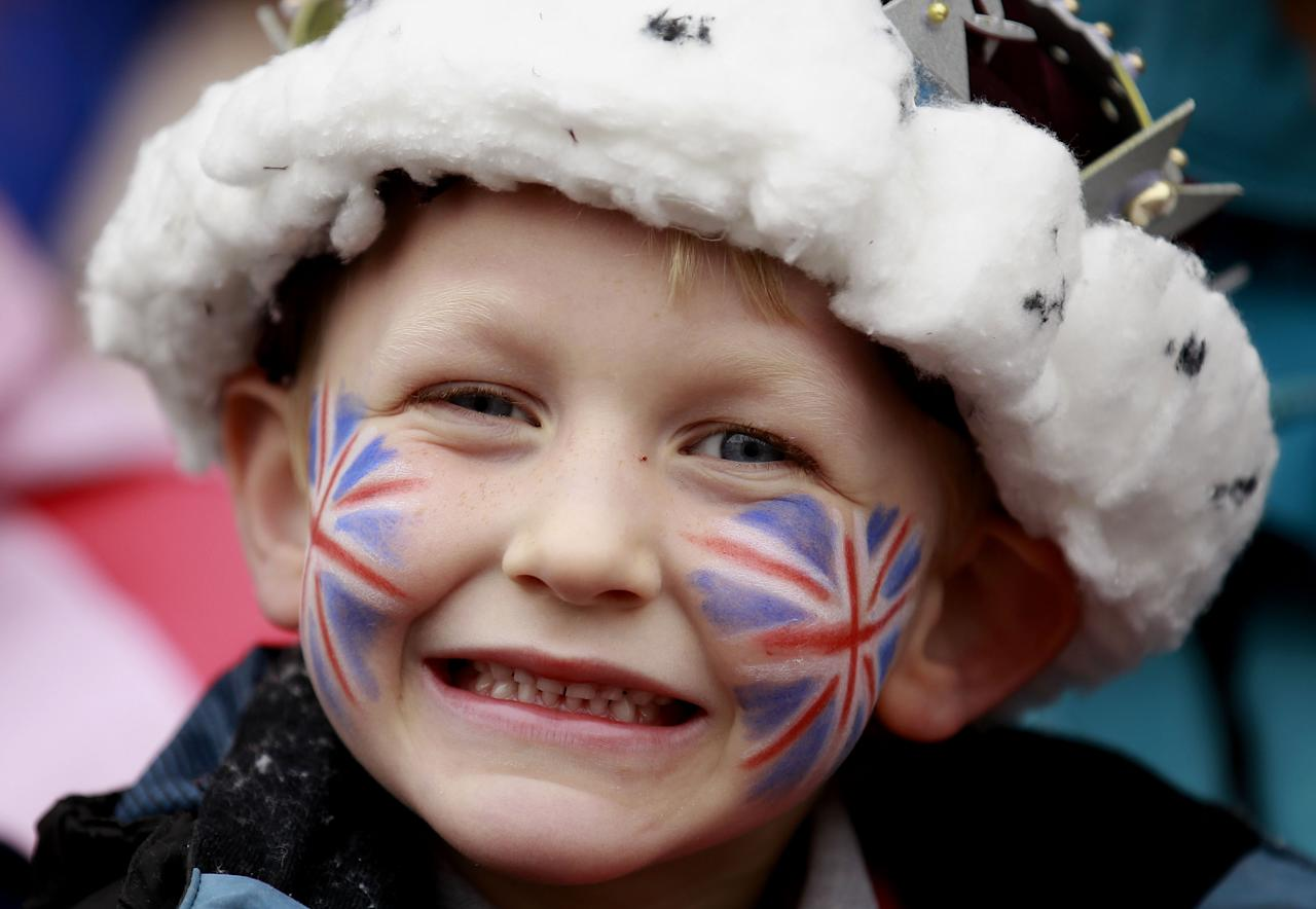 A boy smiles as he waits to catch a view of Britain's Queen Elizabeth II outside a Service of Thanksgiving in Saint Macartin's Cathedral in Enniskillen, Northern Ireland, Tuesday, June 26, 2012. The Queen arrived in Northern Ireland for a two day visit to mark the Queen's Diamond Jubilee. (AP Photo/Peter Morrison)