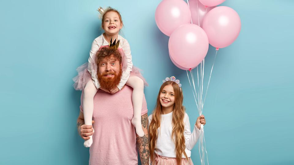 Studio shot of caring father gives piggyback to small daughter, little girl carries air balloons, celebrate birthday, spend free time at home and have fun, isolated over blue background. Ginger family