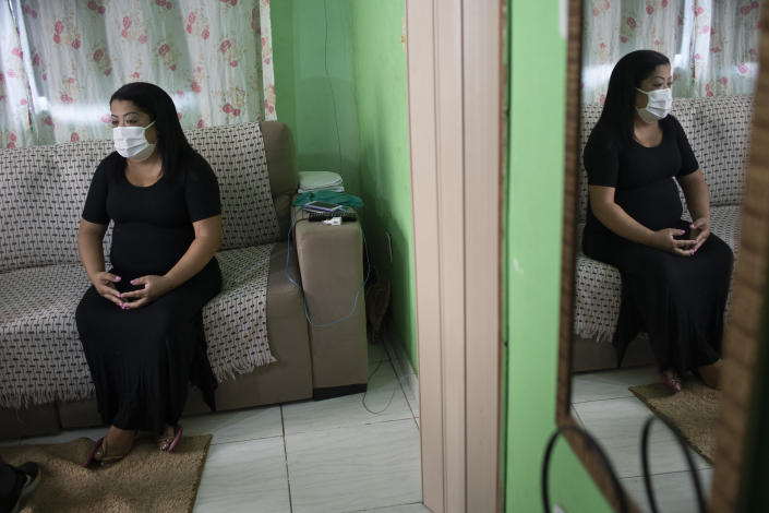 """Nurse Lidiane Melo sits during an interview with The Associated Press at her home in Rio de Janeiro, Brazil, Wednesday, April 14, 2021. In the early days of the pandemic, as sufferers were calling out for comfort that she was too busy to provide, Melo filled two rubber gloves with warm water, knotted them shut, and sandwiched them around a patient's hand, to re-create a loving clasp. Some have christened the practice the """"hand of God,"""" and it is now the searing image of a nation roiled by a medical emergency with no end in sight. (AP Photo/Silvia Izquierdo)"""