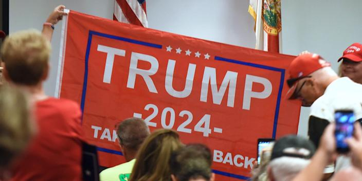 People hold a Trump 2024 flag before U.S. Rep. Matt Gaetz (R-FL) who arrives to address supporters at a Matt Gaetz Florida Man Freedom Tour event at the Hilton Melbourne Beach on July 31, 2021.