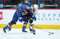Colorado Avalanche defenseman Devon Toews (7) and Los Angeles Kings right wing Alex Iafallo (19) chase the puck during the first period of an NHL hockey game Wednesday, May, 12, 2021, in Denver. (AP Photo/Jack Dempsey)