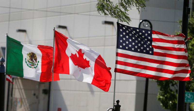FILE PHOTO: Flags of the U.S., Canada and Mexico fly next to each other in Detroit, Michigan, U.S. August 29, 2018. REUTERS/Rebecca Cook/File Photo