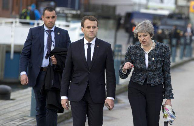 Theresa May speaks with French President Emmanuel Macron as they walk on a pier at an EU summit in Gothenborg