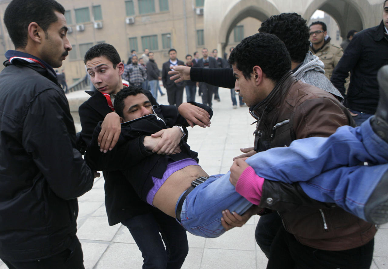 Egyptian Christians carry a man who fell unconscious as mourners crowed the funeral of the late Pope Shenouda III, the patriarch of the Coptic Orthodox Church who led Egypt's Christian minority for 40 years during a time of increasing tensions with Muslims, at Mar Morqos, or St. Mark Coptic Orthodox Church in Cairo, Egypt, Tuesday, March 20, 2012. (AP Photo/Amr Nabil)
