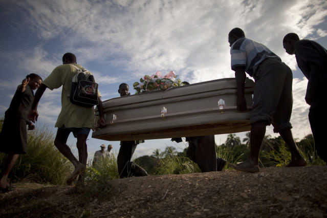 <p>People carry a coffin containing the remains of a relative who died of cholera in Robine, Haiti, Saturday Oct. 23, 2010. A spreading cholera outbreak in rural Haiti threatened to outpace aid groups as they stepped up efforts Saturday hoping to keep the disease from reaching the camps of earthquake survivors in Port-au-Prince. Health officials said at least 208 people had died. (Photo: Ramon Espinosa/AP) </p>