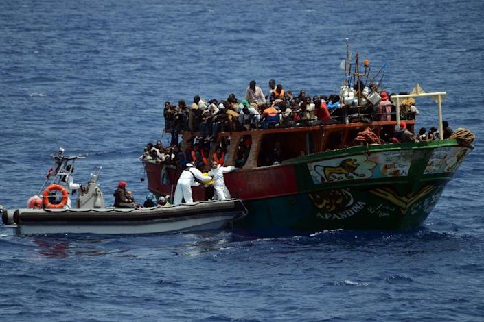 This handout picture taken and released by the French Navy on May 20, 2015 shows members of the crew of the Commandant Birot taking part in a rescue operation of migrants in the Mediterranean Sea (AFP Photo/)