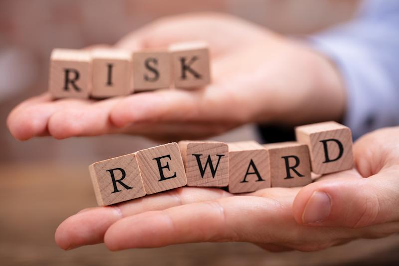 """Two hands holding blocks spelling out """"risk"""" and """"reward"""""""
