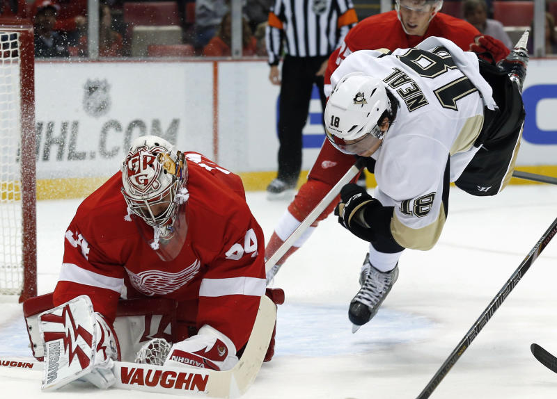 Detroit Red Wings goalie Petr Mrazek (34), of the Czech Republic, stops a shot as Pittsburgh Penguins left wing James Neal (18) tries to get a rebound in the first period of a NHL preseason hockey game in Detroit, Wednesday, Sept. 25, 2013. (AP Photo/Paul Sancya)