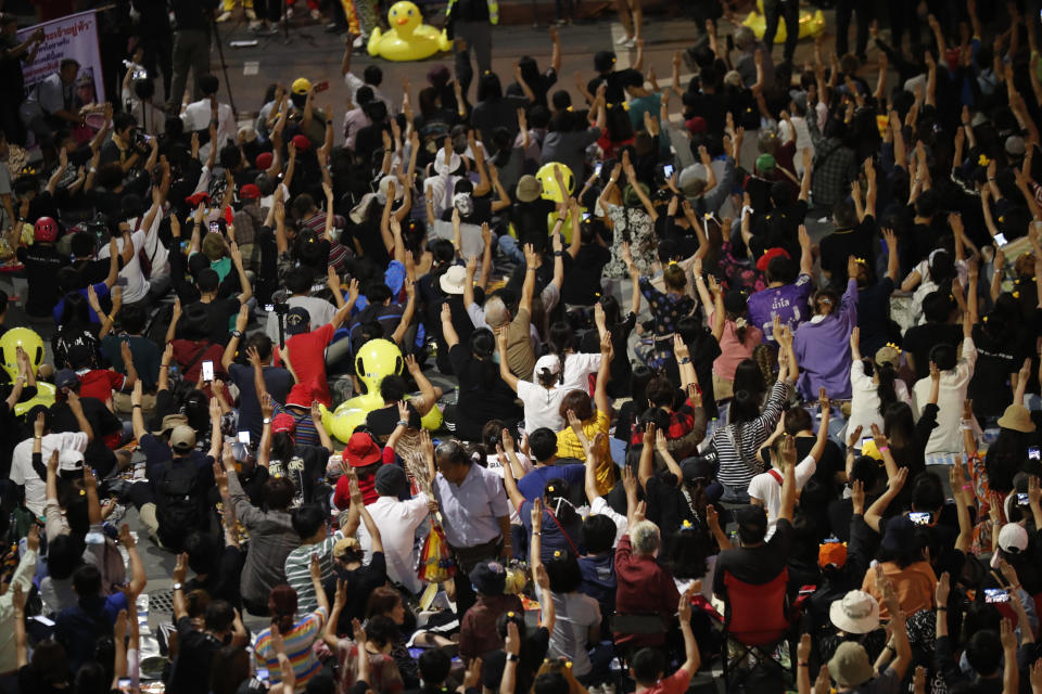 A crowd of protesters flash three-finger protest gestures during a rally Friday, Nov. 27, 2020 in Bangkok, Thailand. Pro-democracy demonstrators are continuing their protests calling for the government to step down and reforms to the constitution and the monarchy, despite legal charges being filed against them and the possibility of violence from their opponents or a military crackdown. (AP Photo/Sakchai Lalit)