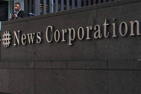 A passer-by stands in front of the News Corporation building in New York in this June 28, 2012 file photo. REUTERS/Keith Bedford/Files