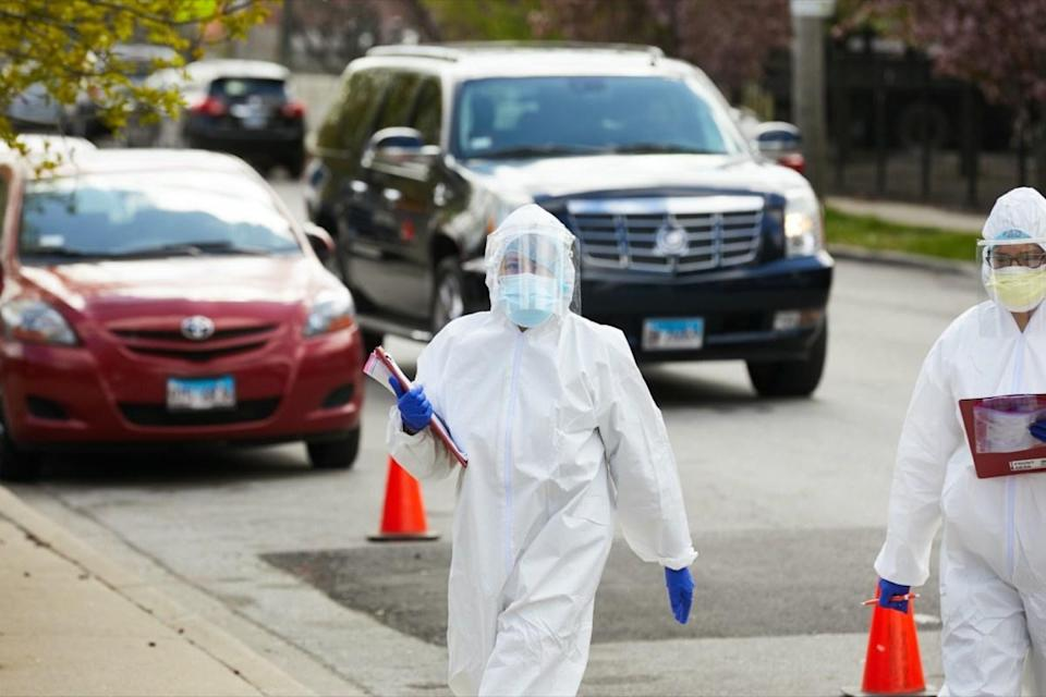 A technician at a drive up testing facility in Chicago walks between cars with patients awaiting testing for coronavirus covid-19
