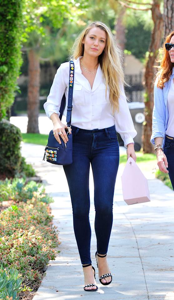 """<p>Blake Lively styles her dark blue skinny Old Navy <a rel=""""nofollow"""" href=""""https://fave.co/2Otj4bW"""">Rockstar Jeans</a> with a classic white button-up shirt, shoulder bag, and open-toe sandals. (Photo: Startraks) </p>"""