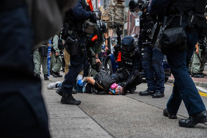 A pro-democracy supporter is detained by riot police Sunday. Source: Getty