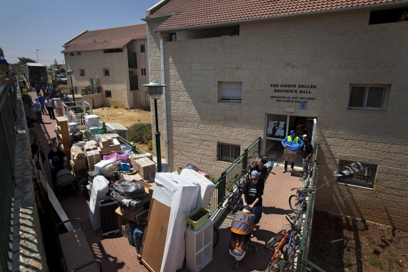 Jewish settlers and movers employed by the Israeli Defense Ministry carry out belongings from settler's apartment in the Ulpana neighborhood in the West bank Jewish settlement of Beit El, near Ramallah, Tuesday, June. 26, 2012. Israel has started on Tuesday to evacuate about 30 families fromthe Ulpanaunauthorized West Bank outpost, following a court order to dismantle the enclave, to be followed by 30 more later this week.Ulpana residents have promised to leave quietly unlike more violent evacuations in the past. (AP Photo/Oded Balilty)
