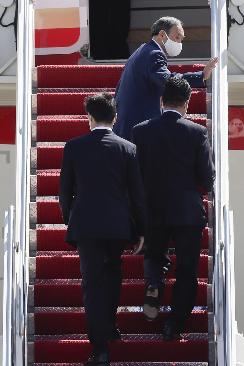 Japanese Prime Minister Yoshihide Suga, top, waves as he boards his plane to depart at Andrews Air Force Base, Md., Saturday, April 17, 2021, after his visit to Washington. (AP Photo/Luis M. Alvarez)