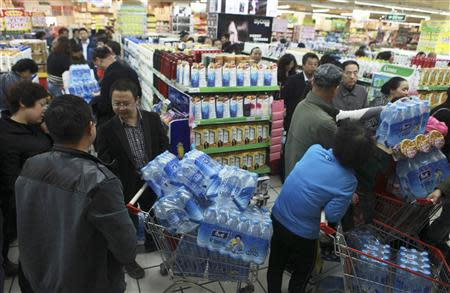 People line up to buy cartons of bottled water at a supermarket after reports on heavy levels of benzene in local tap water, in Lanzhou
