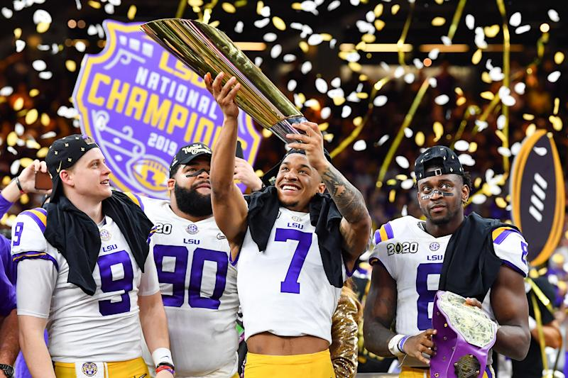 NEW ORLEANS, LOUISIANA - JANUARY 13: Grant Delpit #7 of the LSU Tigers raises the National Championship Trophy with Joe Burrow #9, left, Rashard Lawrence #90, and Patrick Queen #8 after the College Football Playoff National Championship game at the Mercedes Benz Superdome on January 13, 2020 in New Orleans, Louisiana. The LSU Tigers topped the Clemson Tigers, 42-25. (Photo by Alika Jenner/Getty Images)
