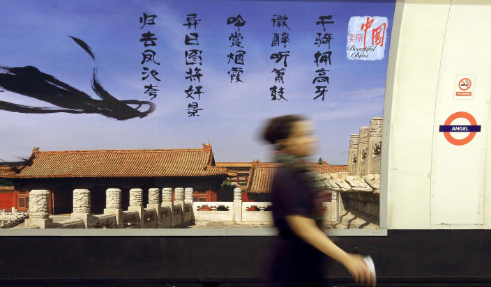 "In this photo taken Wednesday, Sept. 4, 2013, a commuter walks in front of a poster for the China National Tourist Office that's part of its ""Beautiful China"" campaign on display at the Angel tube station in Islington, London. China's new tourism slogan ""Beautiful China"" has been criticized by industry experts who say it illustrates a marketing problem that has led to a weakness in growth in foreign visitors over the past few years. The Chinese characters in black are a North Song Dynasty poem by Liu Yong that describes nobles enjoying beautiful scenes while riding on horse. (AP Photo/Alastair Grant)"