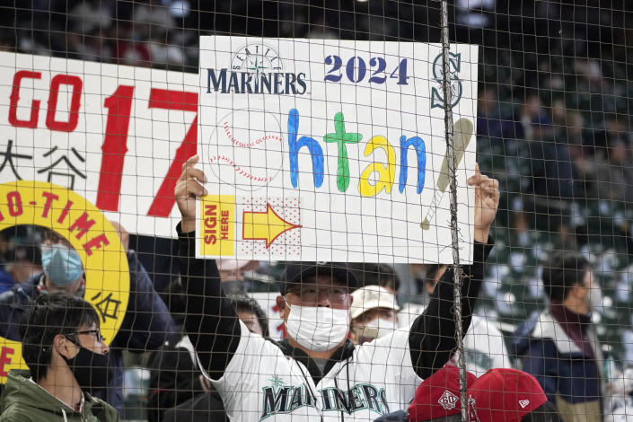 A Seattle Mariners fan holds a sign encouraging the Mariners to sign Los Angeles Angels' Shohei Ohtani in 2024 before a baseball game between the two teams, Sunday, Oct. 3, 2021, in Seattle. (AP Photo/Ted S. Warren)