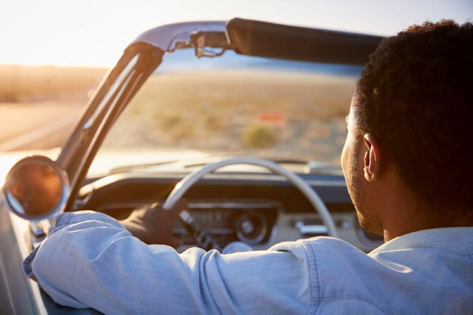 portrait from behind of black man driving a convertible in the desert, changes over 40