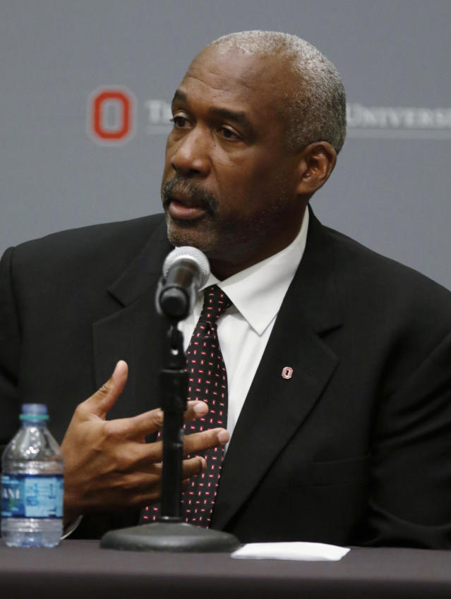 Ohio State University athletic director Gene Smith answers questions during a news conference in Columbus, Ohio, Wednesday, Aug. 22, 2018. Ohio State suspended football coach Urban Meyer on Wednesday for three games for mishandling domestic violence accusations, punishing one of the sport's most prominent leaders for keeping an assistant on staff for several years after the coach's wife accused him of abuse. Athletic director Smith was suspended from Aug. 31 through Sept. 16. (AP Photo/Paul Vernon)
