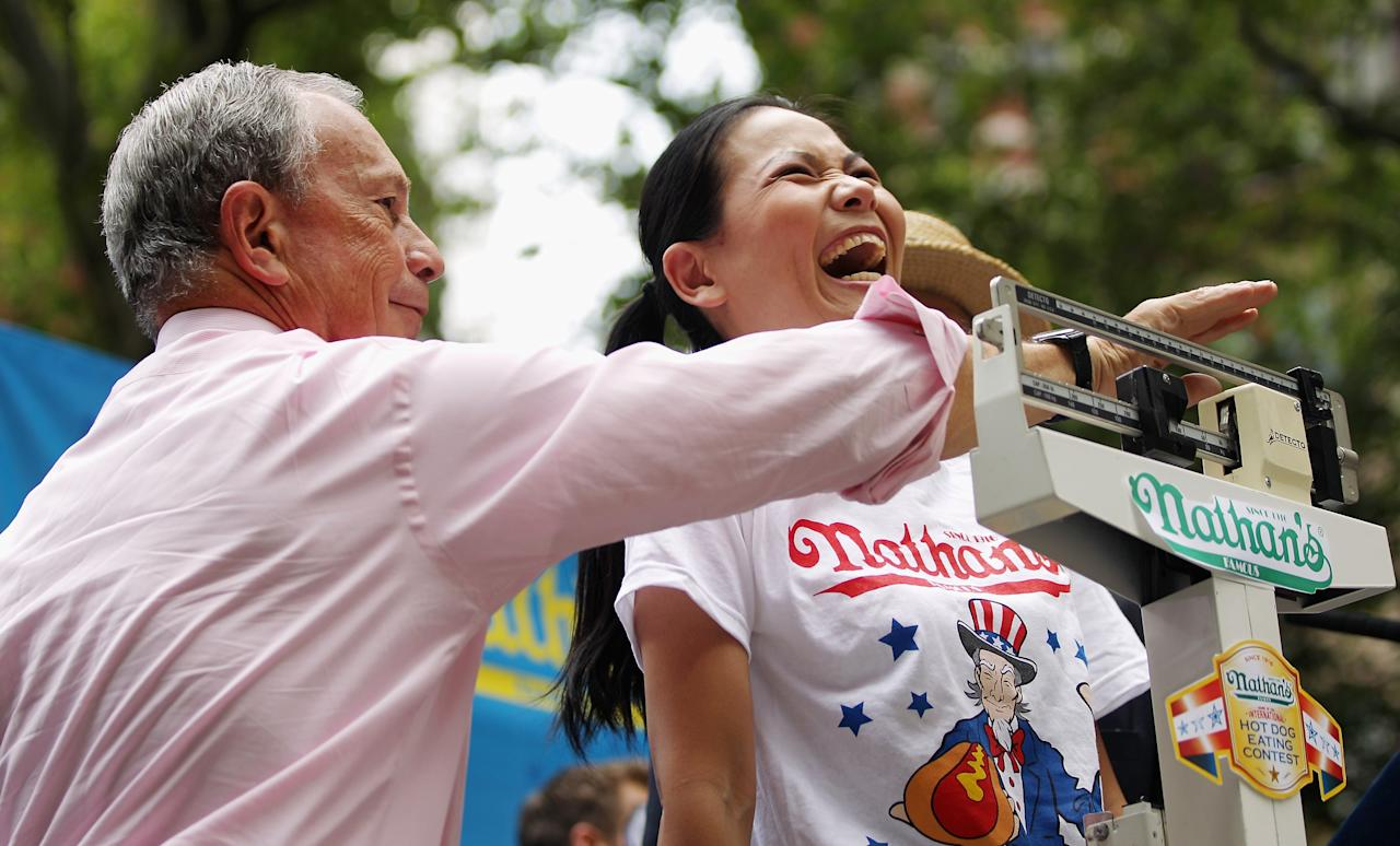 New York City Mayor Michael Bloomberg (L) weighs women's world record holder Sonya Thomas at the Nathan's Famous Fourth of July International Hot Dog Eating Contest weigh-in ceremony on July 3, 2012 in New York City.  The annual hot odg eating event is expected to draw 30,000 fans on July 4, in Coney Island section of Brooklyn. (Photo by Mario Tama/Getty Images)